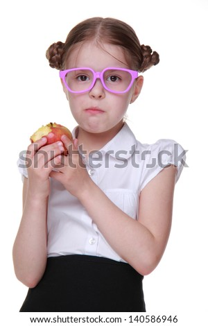 schoolgirl holding red apple on Education theme/beautiful little schoolgirl with fresh organic red apple on healthlife theme