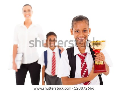 schoolgirl holding trophy in front of teacher and classmate
