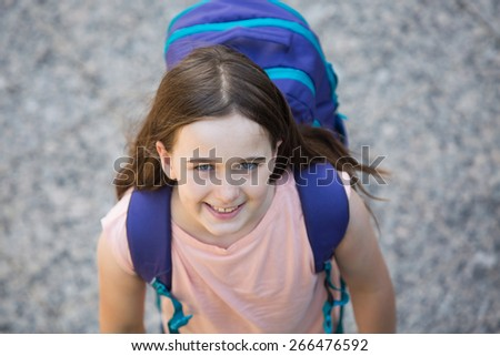 Schoolgirl in a blue shirt with a purple backpack ready for school