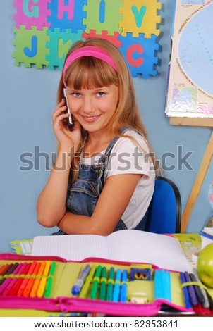 schoolgirl in the classroom talking on mobile phone - stock photo