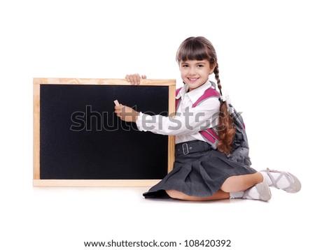 Schoolgirl in uniform sitting on the floor holding the school board - stock photo