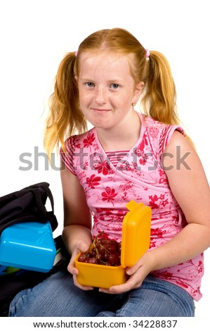 schoolgirl is having grapes as lunch isolated on white