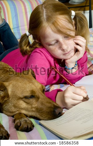 Schoolgirl is making homework together with her dog - stock photo
