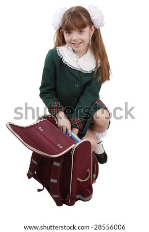 Schoolgirl is packing up schoolbagl. Isolated on white in studio. - stock photo