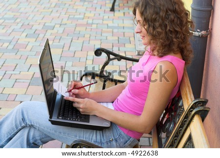 Schoolgirl is preparing to the lesson in schoolyard - stock photo