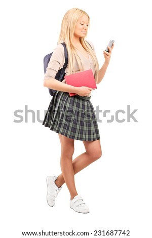 Schoolgirl looking at a cell phone isolated on white background - stock photo
