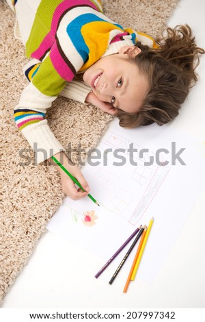 schoolgirl lying on carpet and drawing pictures. waist-up and top view of little girl smiling - stock photo