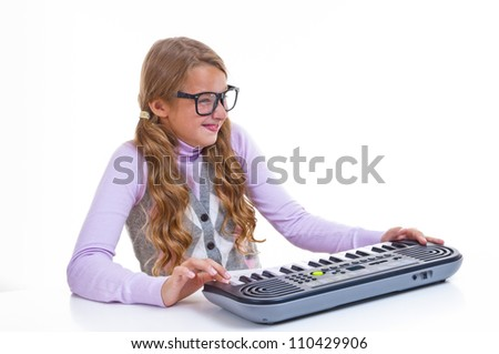Schoolgirl playing on a small synthesizer