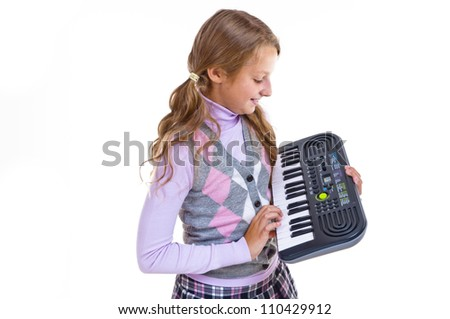 Schoolgirl playing on a small synthesizer - stock photo