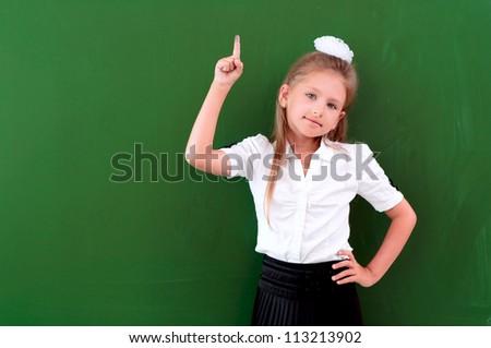 schoolgirl portrait near the blackboards, points finger up - stock photo