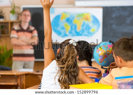 Schoolgirl rising her hand at geography lesson. Rear view - stock photo