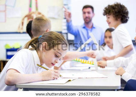 Schoolgirl sitting at a desk with other classmates while working. Her head is down while she concentrates. The teacher can be seen in the background.  - stock photo