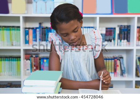 Schoolgirl sitting on table and reading book in library at school