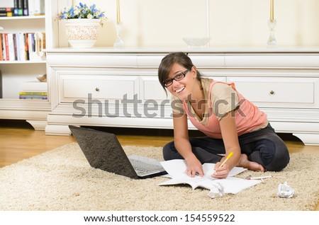 Schoolgirl studying in her room - stock photo