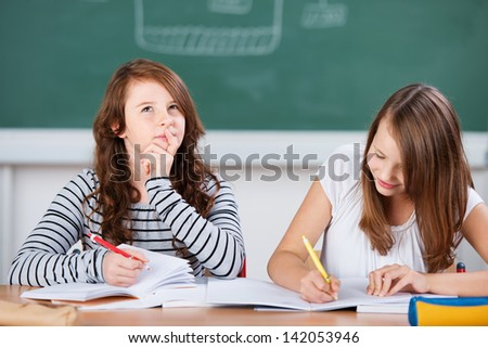 Schoolgirl thinking during an school exercise while her classmate writes in the notebook - stock photo