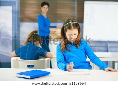 Schoolgirl thinking while filling out test at class, teacher standing in background. - stock photo