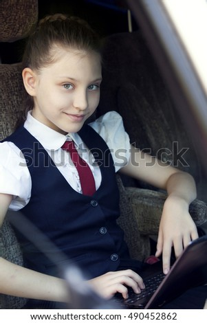 Schoolgirl using digital tablet in car