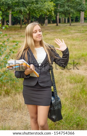 Schoolgirl with notebooks outdoors
