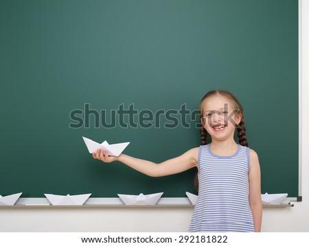 Schoolgirl with origami ship near the school board - stock photo