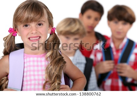 schoolgirl with satchel and boys in background - stock photo