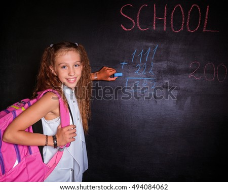 Schoolgirl with school backpack writes on a black blackboard with a piece of chalk. Free space. Black background. School concept