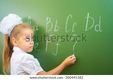 Schoolgirl writes English alphabet with chalk on a blackboard in school classroom. She does not know continuation of the alphabet and wrote a question mark.