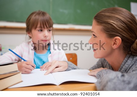 Schoolgirl writing a while her teacher is talking in a classroom - stock photo