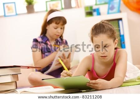 Schoolgirls doing homework at home, writing into exercise books.? - stock photo