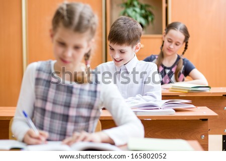 schoolkids work at lesson in classroom - stock photo