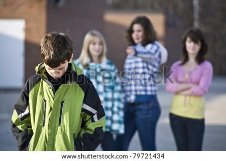 Schoolyard bullies, boy walks away with head down - stock photo