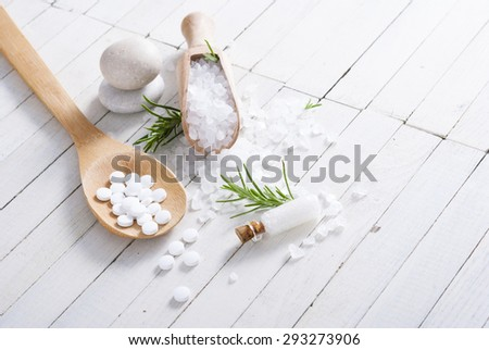 Schuessler salts and salt crystal on white wood table - stock photo