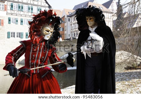 SCHWAEBISCH HALL, GERMANY - FEBRUARY 12: An unidentified couple in costume attend the HALLia VENEZIA event in the old town Schwaebisch Hall, Germany on Feb. 12, 2012. HALLia VENEZIA  was founded in 1998 and was inspired by the Venetian Carnival. - stock photo
