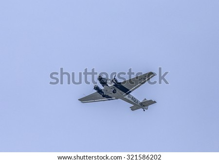 SCHWALBACH, GERMANY - MAY 31, 2015: Junkers Ju52 D-AQUI  flights over the Taunus region at cloudy sky in Schwalbach, Germany. The flight is bookable by Lufthansa as classic flight.