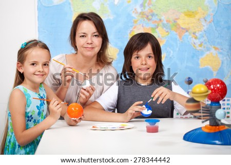 Science and art - kids making the scale model of solar system, painting the planets- focus on the girl face - stock photo