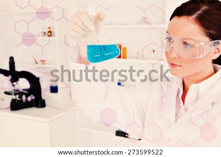 Science and medical graphic against cute female scientist looking at a beaker in a lab - stock photo