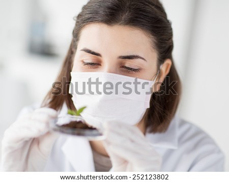 science, biology, ecology, research and people concept - close up of young female scientist wearing protective mask holding petri dish with plant and soil sample in bio laboratory - stock photo