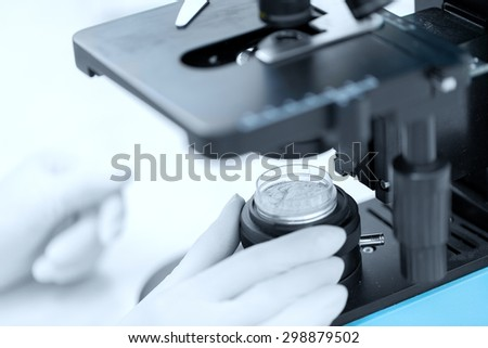 science, chemistry, biology, medicine and people concept - close up of scientist hands with microscope and powder test sample making research in clinical laboratory - stock photo
