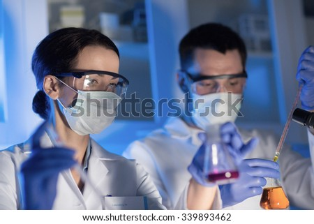 science, chemistry, biology, medicine and people concept - close up of young scientists with pipette and flasks making test or research in clinical laboratory - stock photo