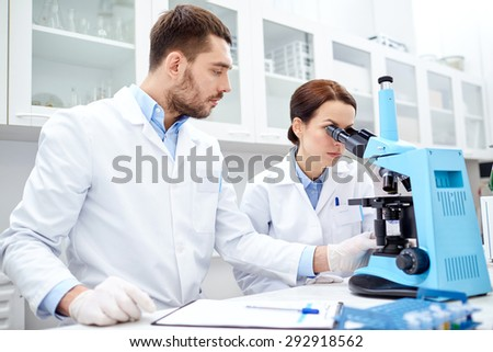 science, chemistry, technology, biology and people concept - young scientists shaking glass with reagent and making test or research in clinical laboratory - stock photo
