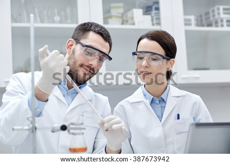 science, chemistry, technology, biology and people concept - young scientists with pipette and test tube making research in clinical laboratory - stock photo