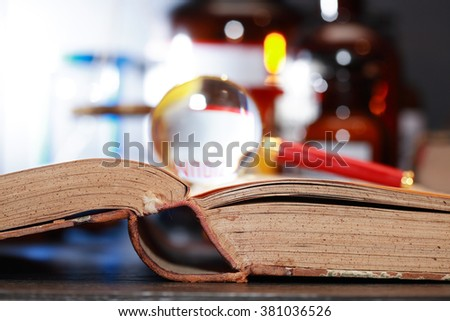 Science concept. Magnifying glass on old book against blurred background with flasks - stock photo