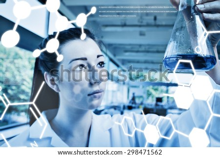 Science graphic against brunette looking at a blue liquide - stock photo