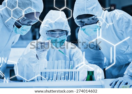 Science graphic against chemist adding green liquid to test tubes with two other chemists watching - stock photo