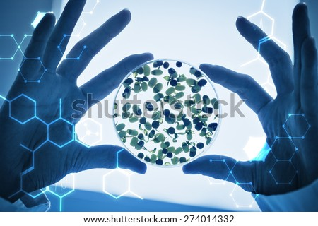 Science graphic against researcher hands holding sprouts in petri dish - stock photo
