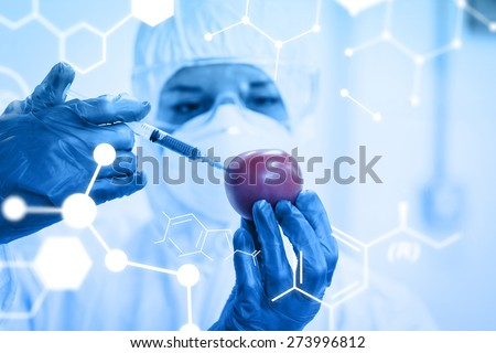 Science graphic against researcher in protective suit injecting tomato at lab - stock photo