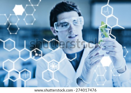 Science graphic against student standing at the laboratory looking at the beaker - stock photo