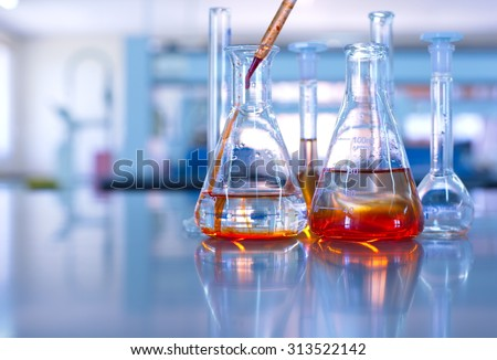 science laboratory glassware orange solution  - stock photo