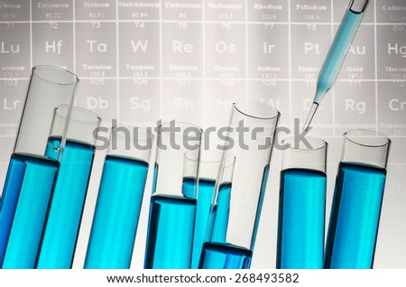 science laboratory test tubes on periodic table background - stock photo