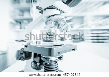 Science microscope on lab bench. Microbiology laboratory. Blue toned image of binocular microscope. Motion blur background - stock photo