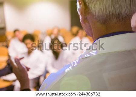 Science professor giving lecture to class at the university - stock photo